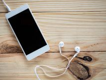 Écouteurs blancs avec des smartphones sur la table et l'espace libre en bois pour le texte et le logo ou les symboles Images stock