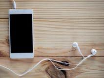 Écouteurs blancs avec des smartphones sur la table et l'espace libre en bois pour le texte et le logo ou les symboles Photos libres de droits