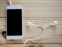 Écouteurs blancs avec des smartphones sur la table et l'espace libre en bois pour le texte et le logo ou les symboles Photo stock