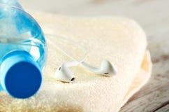 Écouteurs blancs de vue de face et une bouteille de plan rapproché de l'eau sur a Image libre de droits