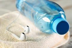 Écouteurs blancs et une bouteille de l'eau sur une serviette éponge Photo libre de droits