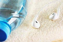 Écouteurs blancs et une bouteille de plan rapproché de l'eau sur une serviette éponge Photo stock