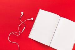 Écouteurs blancs et une magazine de mocup sur un fond rouge photographie stock libre de droits