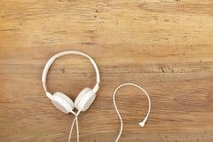 Écouteurs blancs sur le bois Images stock