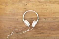 Écouteurs blancs sur le bois Photographie stock