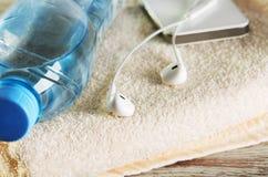 Écouteurs blancs, téléphone et une bouteille de l'eau sur une serviette éponge Photo stock