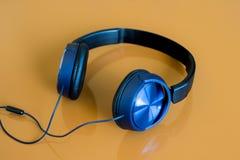 Écouteurs bleus d'isolement sur le brun Photos libres de droits