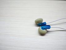Écouteurs bleus mis sur le bureau Images libres de droits