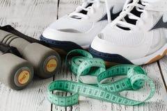 Écouteurs, chaussures et haltères sur le fond en bois Photographie stock libre de droits