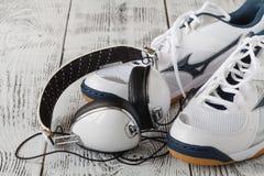 Écouteurs, chaussures et haltères sur le fond en bois Photos stock