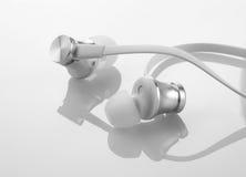 Écouteurs d'écouteurs sur le fond blanc réfléchi Photo stock
