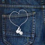 Écouteurs dans une poche arrière de jeans Photo stock