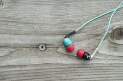 Écouteurs de couleur sur le plancher en bois Photographie stock