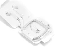écouteurs de Dans-oreille blancs dans le cas particulier avec l'ADA d'Apple de foudre Photographie stock