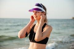 Écouteurs de port de fille de coureur et brassard courant prêts pour la séance d'entraînement photographie stock