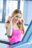 Écouteurs de port de sportive blonde s'exerçant sur le tapis roulant Photos stock