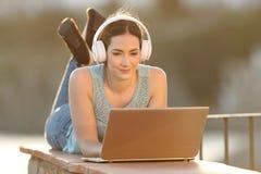 Écouteurs de port de femme observant des médias sur l'ordinateur portable image libre de droits
