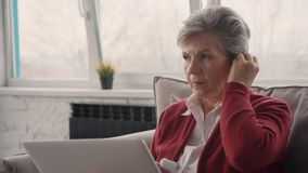 Écouteurs de port de femme de retraité modernes, petits et de confort banque de vidéos