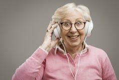 Écouteurs de port de femme supérieure heureuse photographie stock libre de droits