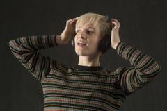 Écouteurs de port de jeune femme blonde et apprécier la musique image stock