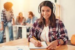 Écouteurs de port de sourire et fabrication de jeune femme des notes Images libres de droits