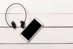 Écouteurs de résistant à l'eau avec Smartphone sur le fond en bois images stock