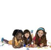Écouteurs de sourire de musique de bonheur d'amies d'enfants ensemble Photographie stock
