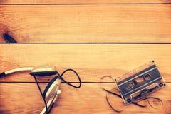 Écouteurs et bande translucide de cassette sonore sur le fond en bois de planches de vintage photo libre de droits