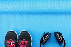 Écouteurs et chaussures de sport sur le fond de tapis de yoga Images stock