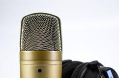 Écouteurs et microphone sur un fond blanc Photo stock