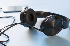 Écouteurs et mobile sur le bleu Fin vers le haut technologie photographie stock libre de droits