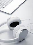 Écouteurs et ordinateur portable sur la table en bois de bureau Images libres de droits