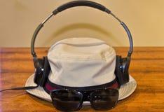 Écouteurs et verres sur Fedora Photographie stock libre de droits