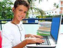 Écouteurs heureux d'ordinateur portatif de garçon d'étudiant d'adolescent Photographie stock libre de droits