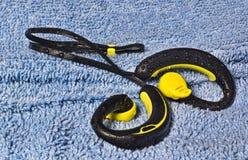 Écouteurs imperméables, jaune et noir, perlés avec de l'eau Photo libre de droits