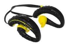 Écouteurs imperméables, jaune et noir, perlés avec de l'eau sur un b Image stock
