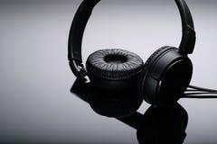 Écouteurs noirs sur a avec le fond photos stock