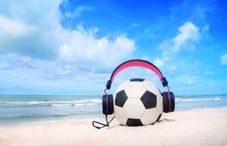 Écouteurs roses, football sur le ciel bleu et fond de plage Photographie stock libre de droits