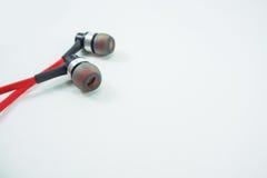 Écouteurs rouges étendus sur un fond blanc images stock