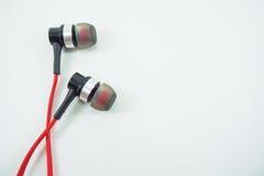 Écouteurs rouges étendus sur un fond blanc photo libre de droits