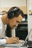 Écouteurs s'usants d'homme utilisant l'ordinateur portatif. photographie stock libre de droits