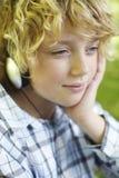 Écouteurs s'usants de jeune garçon à l'extérieur photographie stock