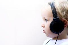Écouteurs s'usants de jeune garçon Photo stock