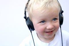 Écouteurs s'usants de jeune garçon heureux Photos stock