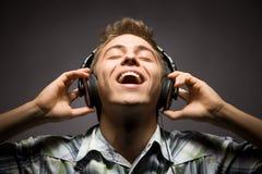Écouteurs s'usants de jeune homme Image stock