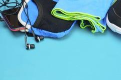 Écouteurs, sac de sport, serviette et chaussures de course sur le tapis de sport Images libres de droits