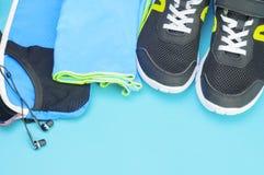 Écouteurs, sac de sport, serviette et chaussures de course sur le tapis de sport Photo stock