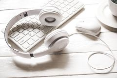Écouteurs sur l'ordinateur portable avec du café blanc de tasse sur la table en bois de bureau Image stock