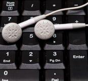 Écouteurs sur le clavier de nombre Photographie stock