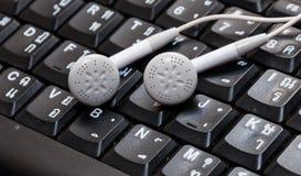 Écouteurs sur le clavier thaïlandais et anglais Photos libres de droits
